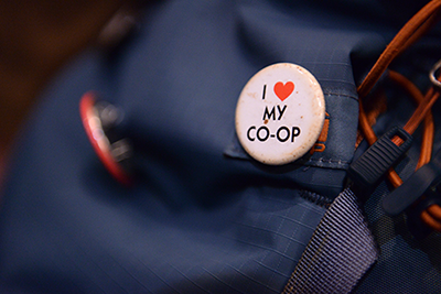 """A closeup of a navy backpack with a round, white """"I heart my co-op"""" button."""