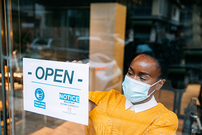 A Black small business owner places an open sign with COVID-19 restrictions in her store window.