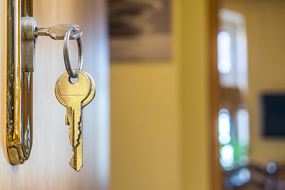 Closeup of a key in the door of a new home. Interior of home is seen in the background.