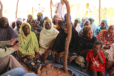 Image shows members of a women's group in Niger working together to address the challenges their community faces.