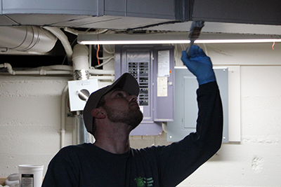 Image shows a worker sealing the duct system in a house to maximize energy savings.