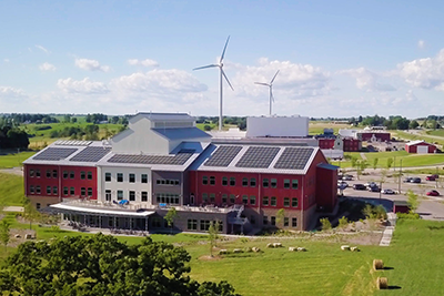 Organic Valley headquarters is seen with solar panels on its roof and wind turbines in the background.