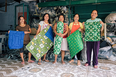 Image includes five women owners of a worker co-op posing with their products.