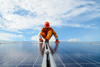 Image shows a man wearing an orange hardhat and uniform working on a solar power station.