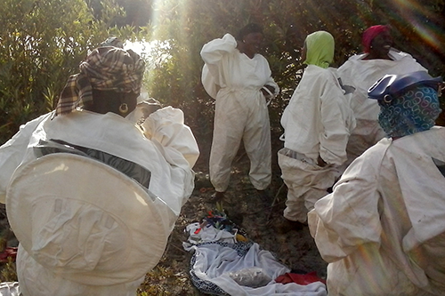 Missirah women put on beekeeping suits before hive inspections. [photo: Erin Schneider]