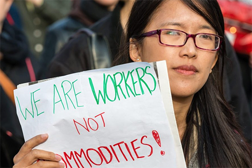 A woman joins a May 1 workers' march in Toronto, Canada. [photo courtesy Co-operative News]