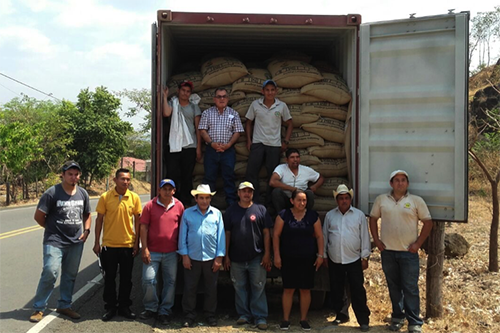 San Carlos Dos Cooperative member-owners stand next to their inaugural coffee export, destined for London.