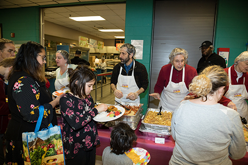 Volunteers hand out food to furloughed federal workers and their families at a community potluck in Maryland last week. [photo: Dave Asche/NPR]