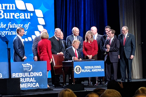 President Trump signs two executive orders to facilitate rural broadband after an address to the American Farm Bureau conference in Nashville. [photo: Mike Knotts]