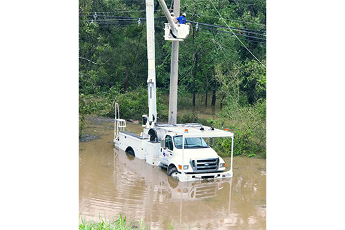 With a truck nearly up to its doors in water, a team from Victoria Electric Cooperative works to bring back power. [photo: Victoria Electric Cooperative]